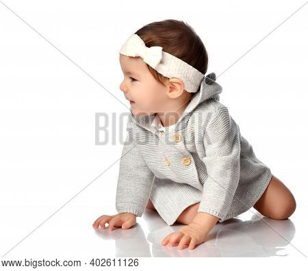 Happy Smiling Curious Baby In Knitted Wear, Headband Isolated Portrait. Excited Infant Child Crawlin