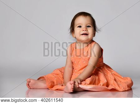Portrait Of Sweet Infant Girl Girl Dressed In Dress Isolated On Gray In Studio. A Baby Toddler Dress