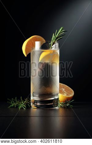 Cold Refreshing Drink With Ice, Lemon, And Rosemary. The Frozen Glass With A Cocktail Gin And Tonic