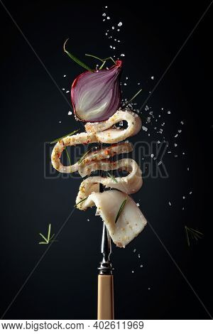 Slice Of Spicy Lard With Onion Sprinkled With Salt And Rosemary. Spicy Lard On A Dark Background.