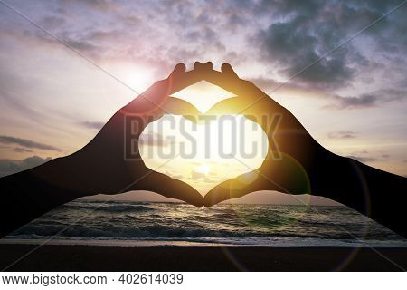 Valentines's Day Concept, Silhouette Hand Make Heart Shape With Seascape Sky And Sunlight.