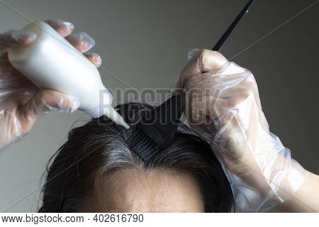 Closeup Woman Hands Dyeing Hair Using Black Brush. Middle Age Woman Colouring Dark Hair With Gray Ro