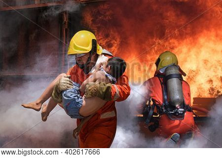 Firefighter Holding Child Boy To Save Him In Fire And Smoke,firemen Rescue The Boys From Fire.