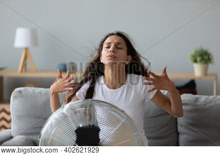 Funny Overheated Woman Enjoying Fresh Air, Cooling By Electric Fan