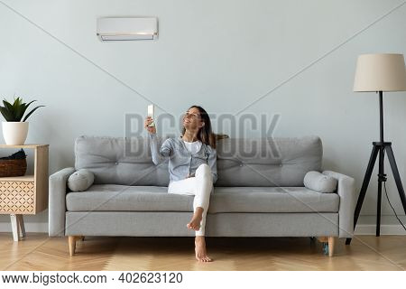 Smiling Woman Using Air Conditioner Remote Controller, Sitting On Couch
