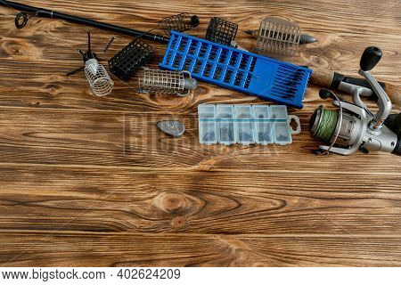 Flat Lay With Fishing Tackle, Fishing Rod And Plastic Box With Fishing Tackle And Hooks, Feeders On