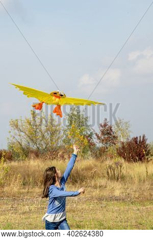 Teenage Girl Flying A Yellow Kite. Beautiful Young Girl Kite Fly. Happy Little Girl Running With Kit