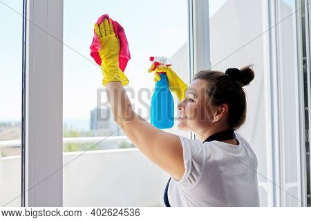 House Cleaning, Mature Woman In Rubber Gloves Wearing An Apron Washing Windows With Rag And Spray Wi