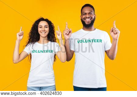 Look There. Female And Male Volunteers Couple Pointing Fingers Up Advertising And Recommending Somet