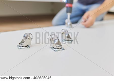 Furniture Assembly Parts, Furniture Wheels Close-up. Worker Hands Assembling Furniture Using Profess