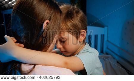 Portrait Of Little Upset And Sad Toddler Boy Hugging And Kissing His Mother Before Going To Sleep At