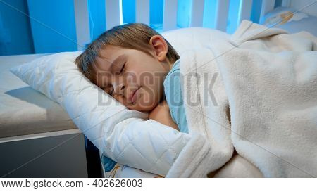 Little Toddler Boy Sleeping On Bed At His Room At Night. Child Resting And Dreaming At Night