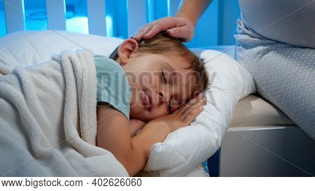 Closeup Of Little Sleeping Boy In Bed And Loving Mother Stroking Him On Head. Cute Toddler Boy Sleep