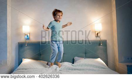 Happy Laughing And Smiling Toddler Boy In Pajamas Skipping And Jumping Up High On Parents Bed At Nig