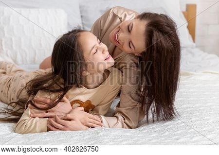 Love Between Parent And Child. Joyful Young Woman Hugging Her Cute Teenage Daughter On Bed At Home.
