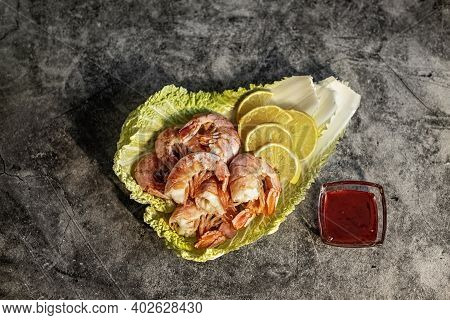 On The Leaves Of Peking Cabbage, King Prawns With Lingonberry Sauce And Lemon. The Concept Of Health