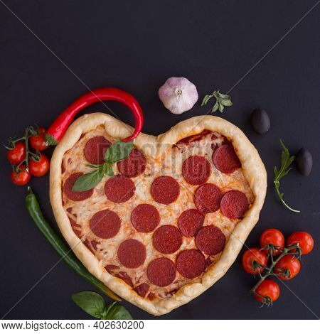 Pizza Heart Shaped With Pepperoni With Ingredients On Black Background. Concept Of Romantic Love For