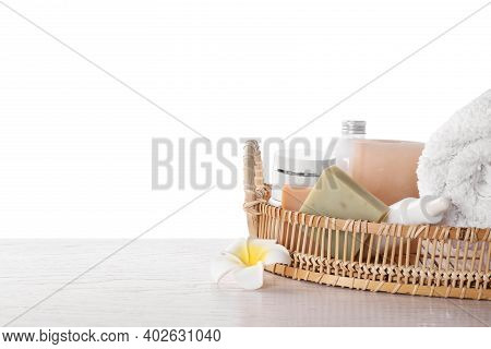 Wicker Tray With Towel, Plumeria Flower And Toiletries On White Wooden Table. Spa Treatment