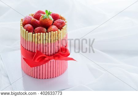 Fresh Strawberry Cake With Strawberry Biscuit Sticks And Red Ribbon On White Cloth Background.  Vale