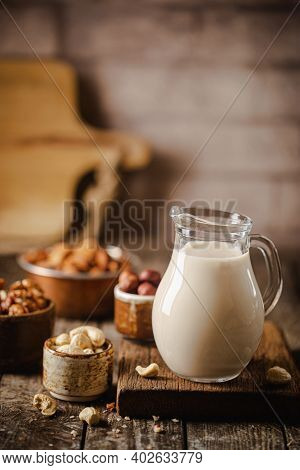 Vegan Alternative Non Dairy Milk From Cashew Nuts In A Jug With Various Nuts On Wooden Table