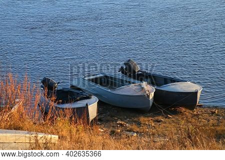 Different Old Boats Are On The Riverbank In Autumn Sunny Day In Village. Boats With And Without Moto