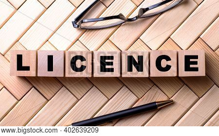 The Word Licence Is Written On Wooden Cubes On A Wooden Background Next To A Pen And Glasses.