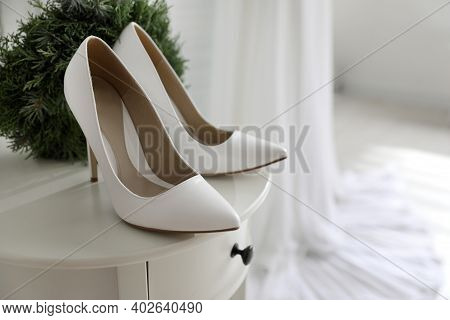 Pair Of White High Heel Shoes, Wreath And Blurred Wedding Dress On Background, Space For Text