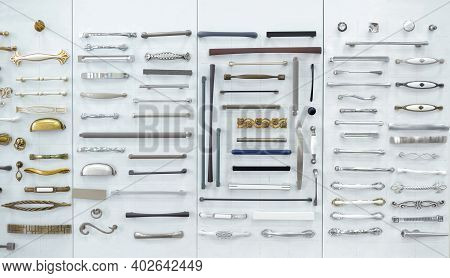 Big Selection Of Handles Cabinets Parts On A White Background Shop Window. Samples Of Metal And Stai