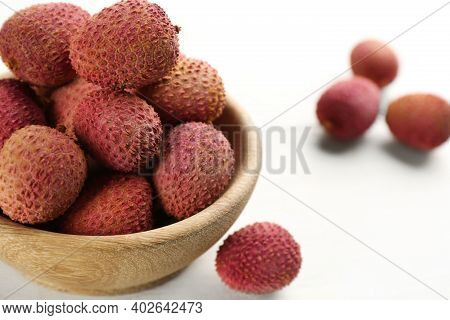 Fresh Ripe Lychees In Bowl On White Wooden Table, Closeup. Space For Text