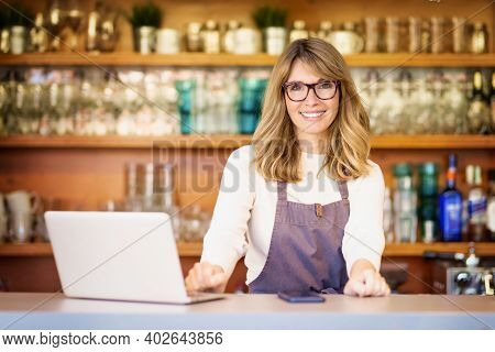 Attractive Small Business Owner Mature Businesswoman Using Laptop While Standing In The Cafe