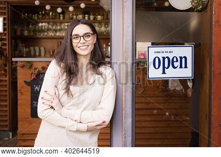 Female Owner Of Coffee Shop Standing In The Doorway
