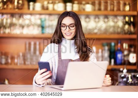 Shot Of Happy Female Coffee Shop Owner Standing In The Coffee Shop And Working. Young Waitress Using
