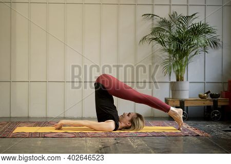 Middle Aged Woman Yoga Asanas. Instructor Shows A Pose From Yoga. Woman Practicing Yoga Concept Natu