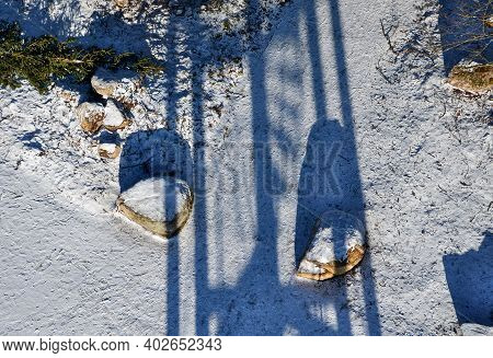 Snowy Parking From Above. Large Stones Delimit The Parking Space. A Barrier Made Of Giant Tribes Tha