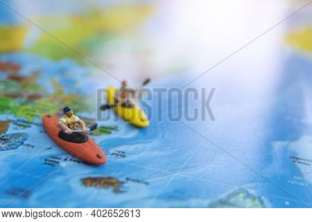 Miniature People: Traveler Sitting On Board Canoe And World Map. Travel, Vacation And  Summer Concep