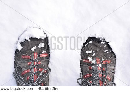 Feet In Hiking Boots Stepping On The Snow. Black, Gray And Red Boots. Snow Storm Called Filomena. La