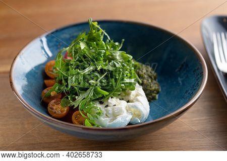 Italian Fresh Cheese Burrata With Colorful Cherry Tomato Salad, Arugula And Basil With Pesto Sauce