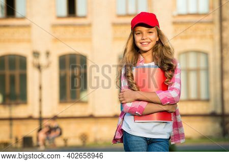 Non-formal Education. Happy Child Hold Books In Schoolyard. School Library. Casual Fashion Style. No