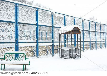 Snow-covered Courtyard Of A Residential Quarter: High Fence Sports Basketball Court, Bench, Gazebo.