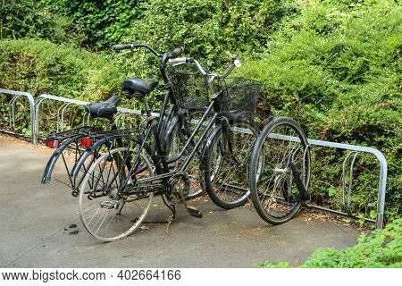 Several Damaged And Destroyed Bikes Standing On A Street In A Bike Stand With Missing Parts. The The