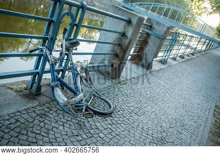 A Broken Bike Is Locked To The Railing At The River In The City Center. The Front Wheel Was Stolen.