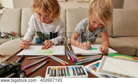 Focused Little Siblings, Boy And Girl Drawing On Paper Using Marker Pen While Spending Time Together