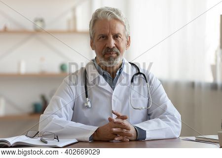 Portrait Of Pleasant Professional Older Mature Gp Physician.