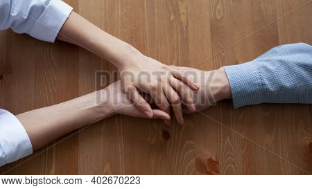Young Compassionate Female Nurse Holding Hand Of Old Patient.