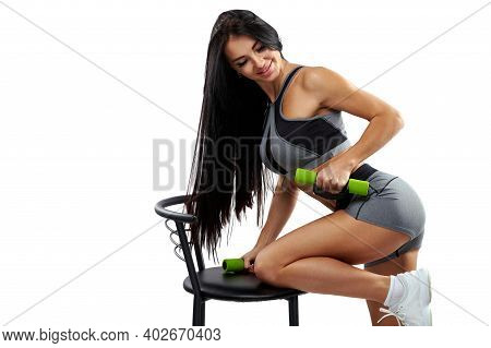 Beautiful And Attractive Fit Woman Pumping Triceps Using Dumbbells Isolated On A White Background