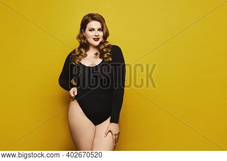 Beautiful Plus-size Model Woman With Bright Makeup In Black Bodysuit Posing Over Yellow Background,