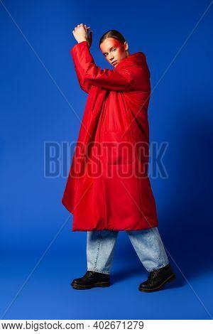 Trendy Female Dancing On Tiptoes Against Blue Background
