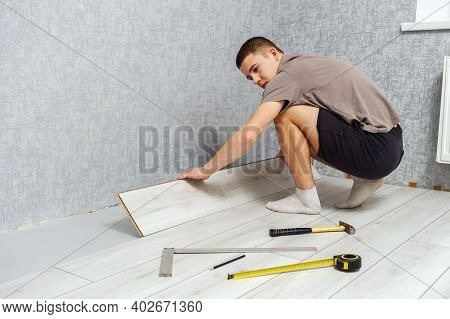 Young Male Repairman Is Laying Wooden Panel Of Laminate Floor Indoors On The Knees. Laminate Floorin