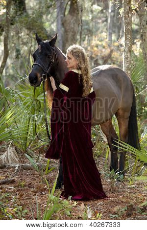 beautiful woman in medieval dress and arabian horse in forest