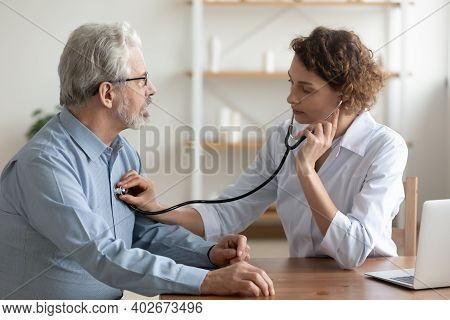 Focused Young Female Cardiologist Listening Heartbeat Of Old Patient.